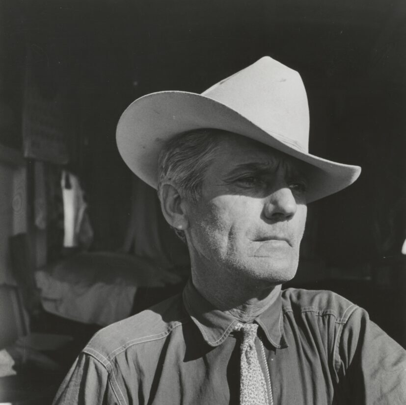 grayscale photography of man wearing cowboy hat and button-up long-sleeved shirt